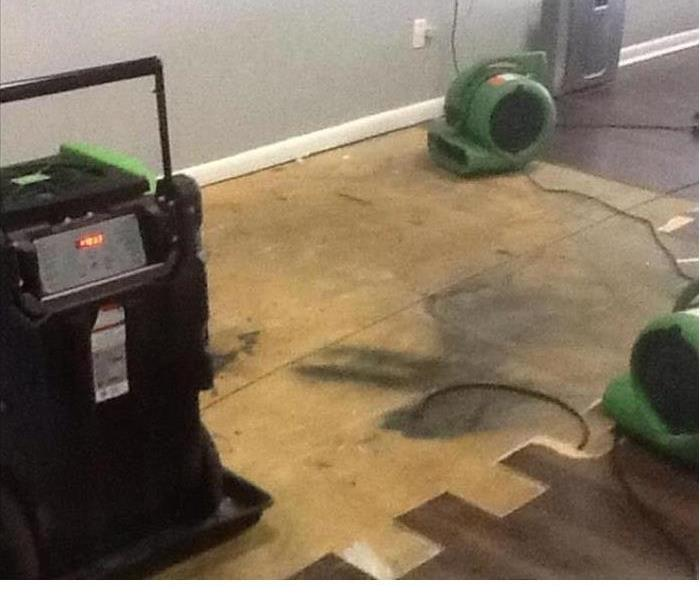 water damaged partially removed flooring and drying equipment