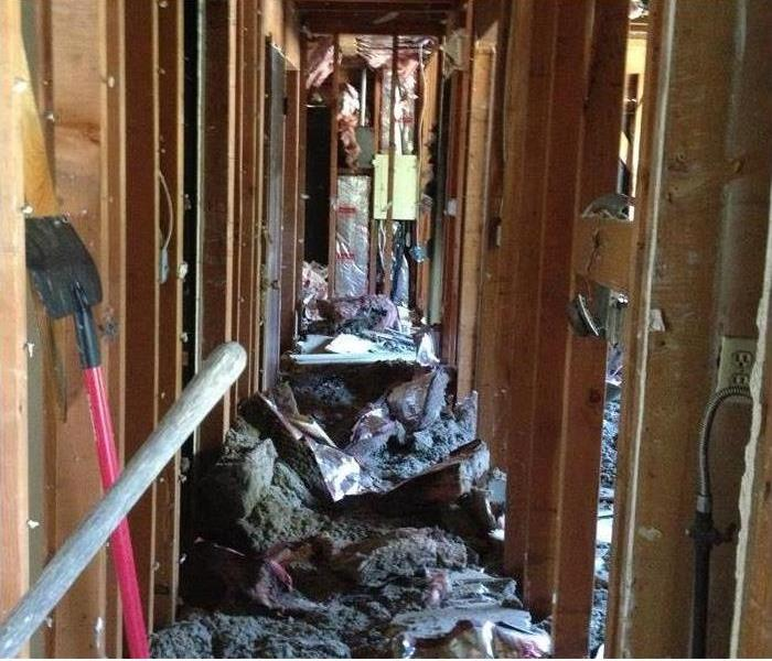fire damaged debris in a hallway without drywall