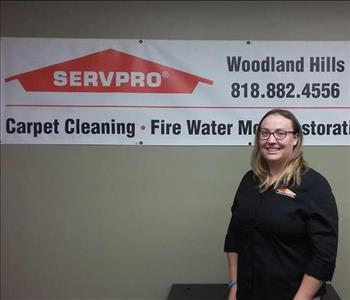 photo of female employee wearing glasses and standing in front of a SERVPRO sign