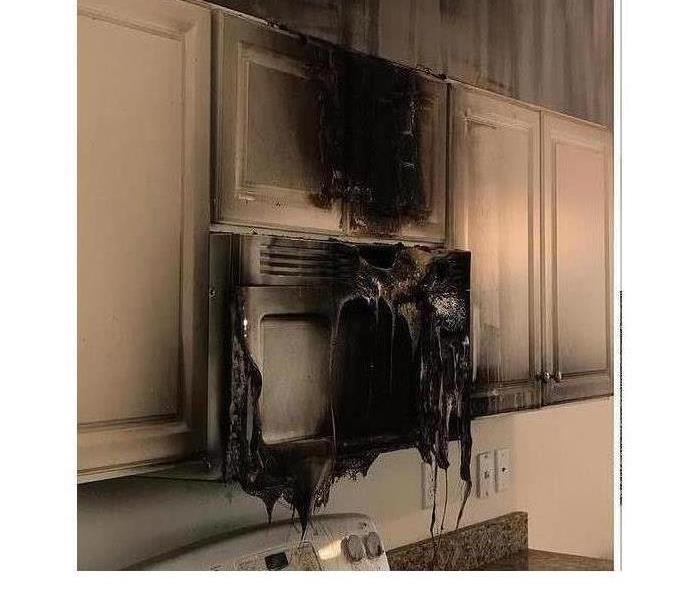 fire melted microwave in a white kitchen
