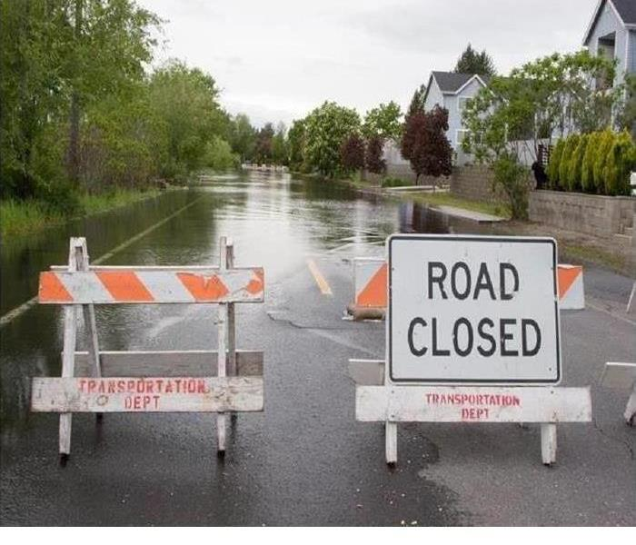 Flooded street with road closed sign